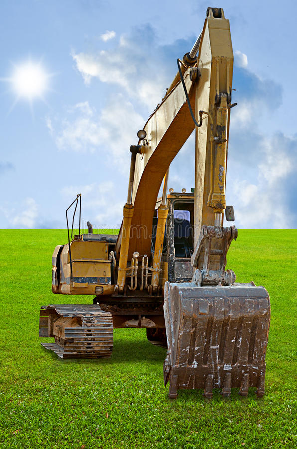 Track-type loader excavator machine on grass field stock images