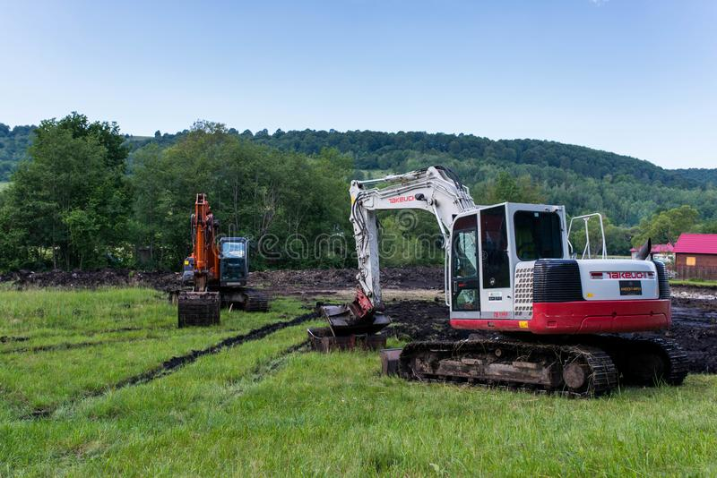 Tracked excavators near a small river , working on the creek bed. Odorheiu Secuiesc, Romania- 16 June 2019: Tracked excavators near a small river , working on royalty free stock photography