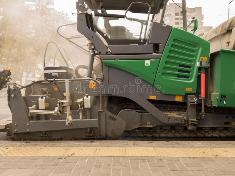 Tracked paver. Industrial pavement truck laying fresh asphalt on construction site. Asphalt a new on the road texture and a stock photography