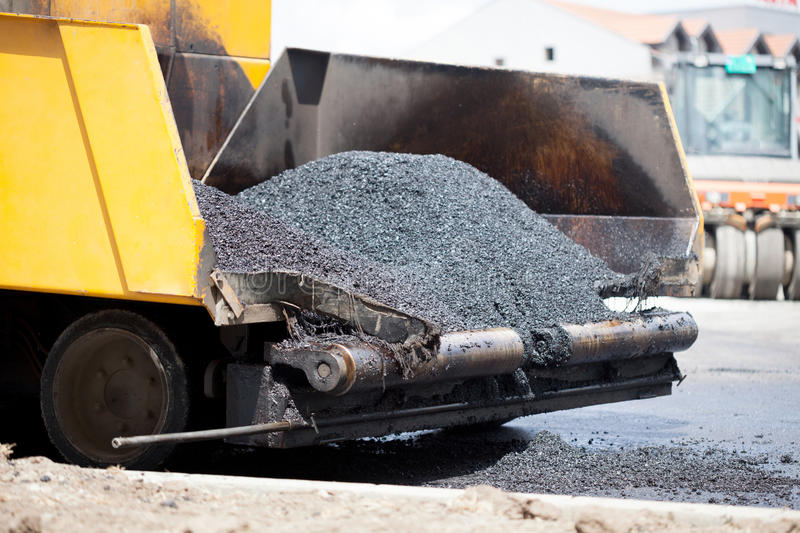Tracked paver laying fresh asphalt pavement during road constru stock images