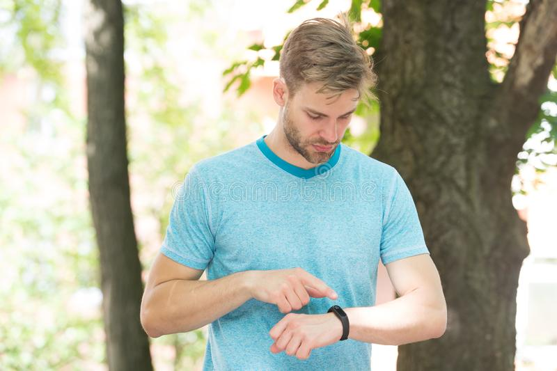 Tracking his training with a sports watch. Handsome athlete using smart watch during training outdoor. Sportsman stock photography