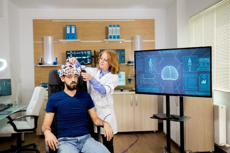 Trackinggegevens van de arts die worden verzonden door een hoofdtelefoon met een hersengolven stock foto