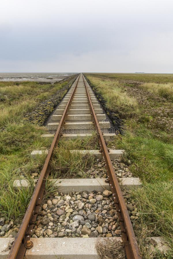 Tracks align at horizon. Close to the sea with concrete ties on a dam royalty free stock photos