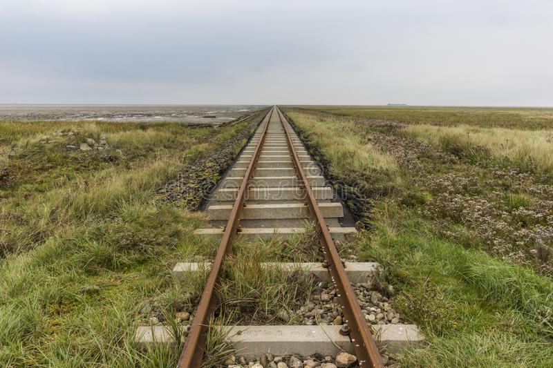 Tracks align at horizon. Close to the sea with concrete ties on a dam royalty free stock image