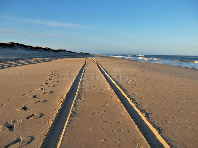 Tracks in the Sand on Hatteras Island. Footprints and tire prints in the sand along the beach of Cape Hatteras National Seashore in the North Carolina Outer royalty free stock photography