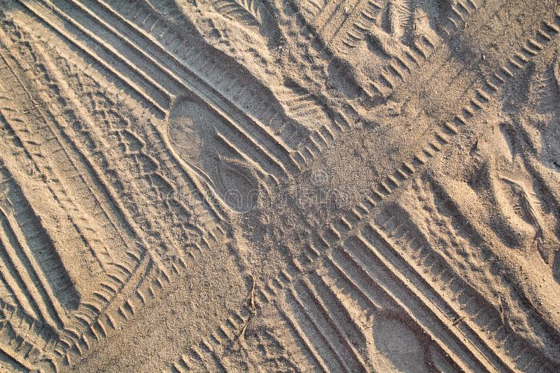 Tracks in sand. Part of prints and tracks of tire, foot, feet, sun sea slippers in beach sand. royalty free stock photography