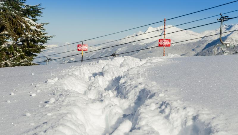 Tracks in the snow beside a ski area boundary sign. royalty free stock images