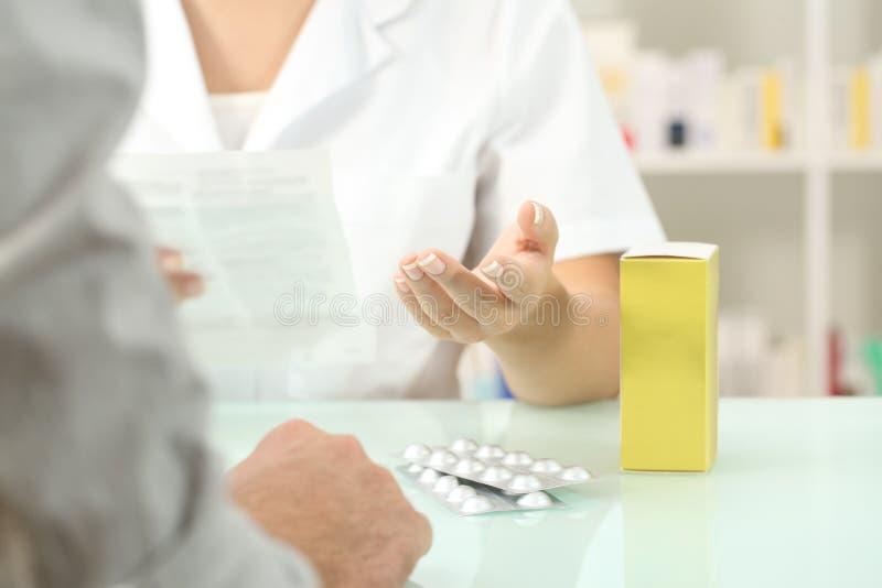 Tract de lecture de pharmacien d'une médecine à un patient photo stock