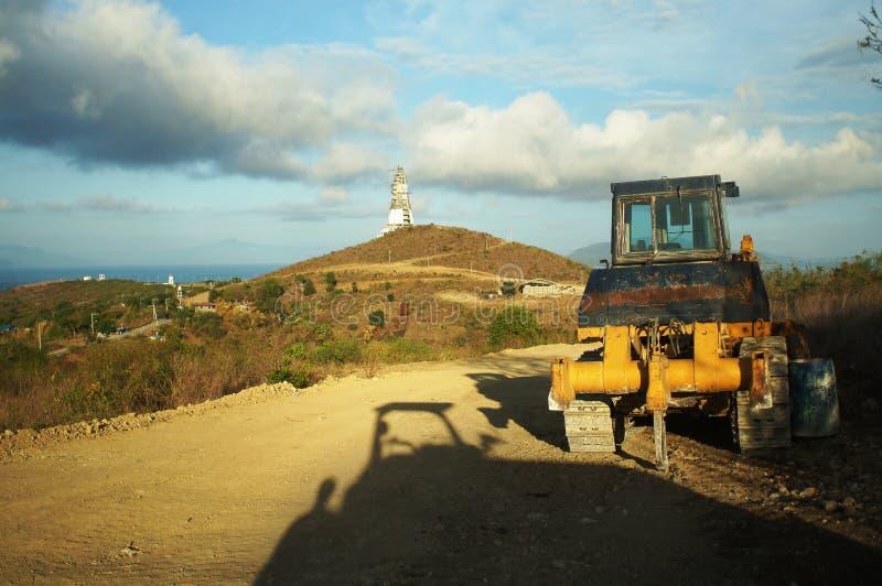 Tracteur à chenilles garé utilisé pour construire la route pour la statue de construction de but multi gigantesque de Vierge Mari photographie stock libre de droits