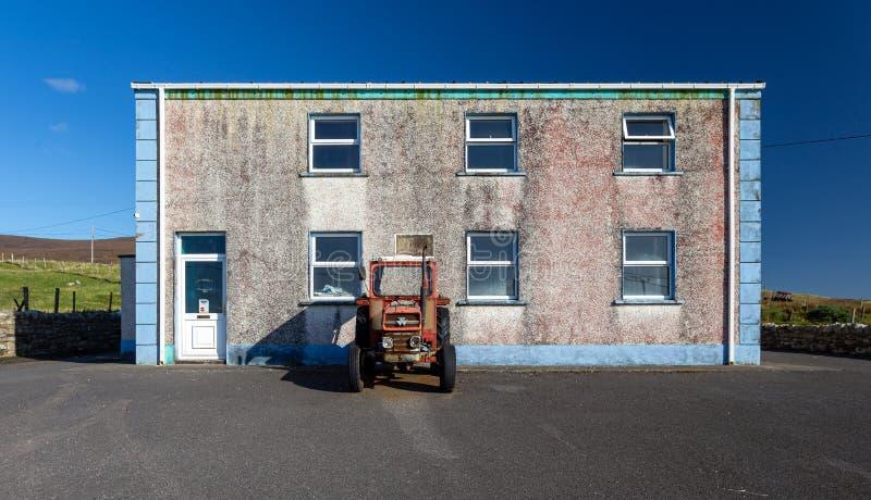 Tracteur à la porte d'une maison abandonnée photos stock