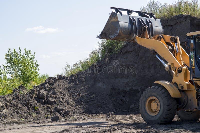 tracteur à roues muni d'un godet nettoie la couche de sol pour la construction ultérieure images libres de droits