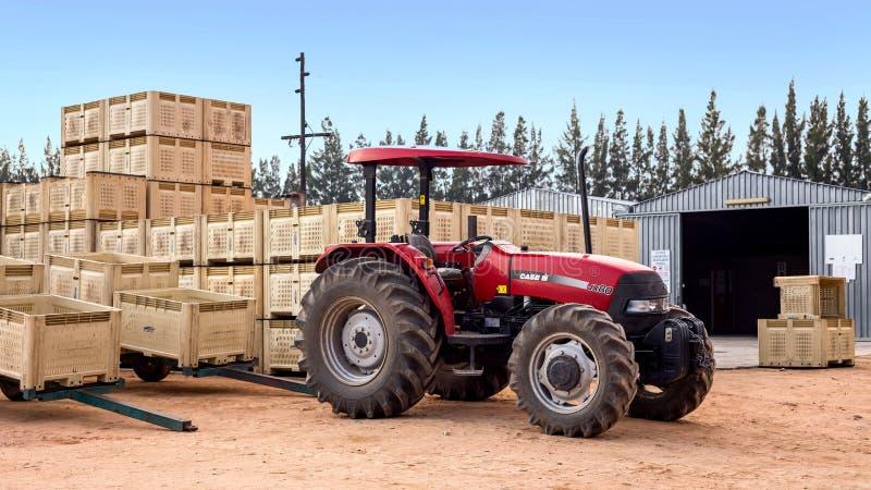 Tracteur avec des caisses de fruit à la ferme photos stock