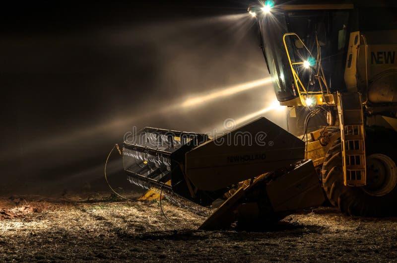 Tracteur avec des lumières dessus la nuit après la récolte de soja photographie stock
