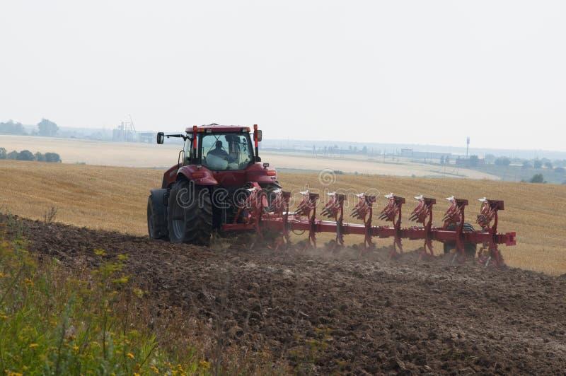 Tracteur avec la charrue sur des processus de terres arables photo stock