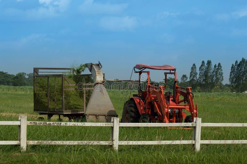 Tracteur avec la tondeuse à gazon de machine de fauchage à la ferme photographie stock