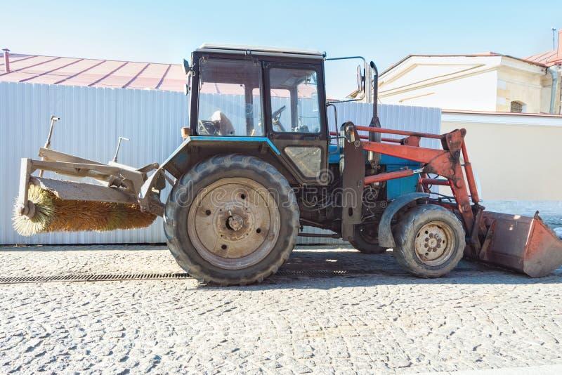 Tracteur avec un balai pour le balayage des routes Le tracteur est sur la vieille rue de ville image libre de droits