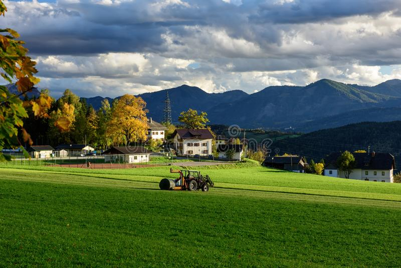 Tracteur avec un emballage de balle préparant pour envelopper une balle de foin Village Obermillstatt, Carinthie, Autriche photos stock