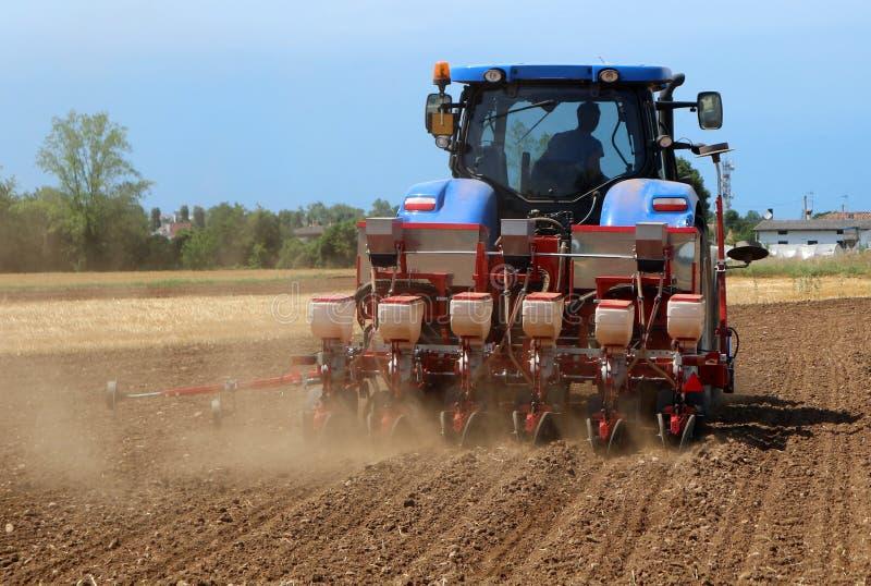 Tracteur avec une machine pneumatique de perceuse de graine sur un champ fraîchement labouré dans l'été image libre de droits