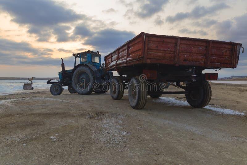 Tracteur avec une remorque livrant le sel extrait d'un lac de sel image stock