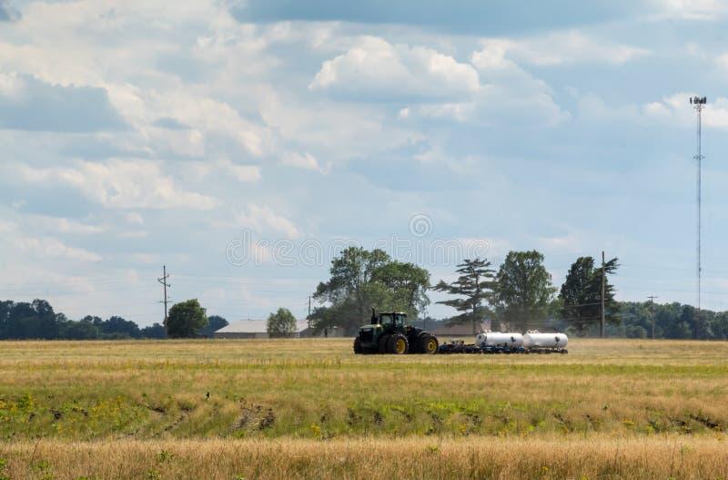 Tracteur cultivant et traitant des champs de ferme en Illinois pour la culture en retard plantant la saison images stock