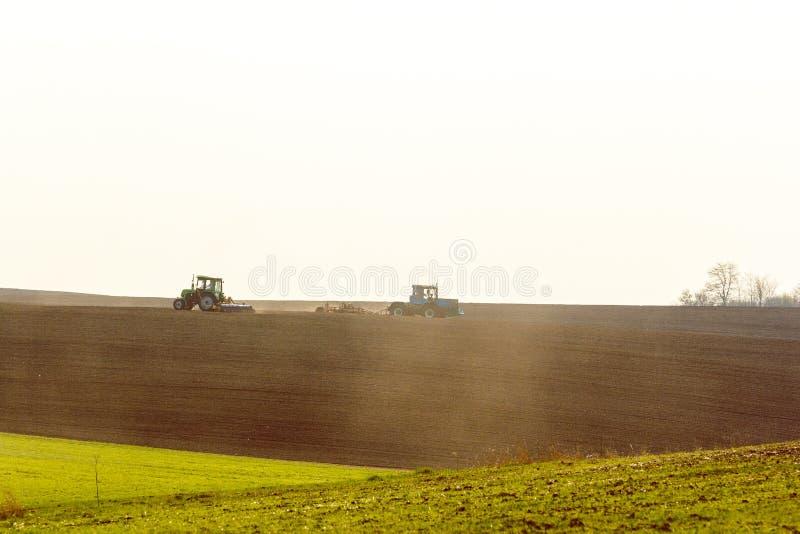 Tracteur cultivant le champ au ressort image stock