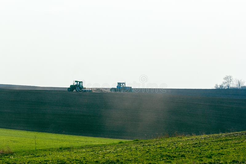 Tracteur cultivant le champ au ressort photographie stock