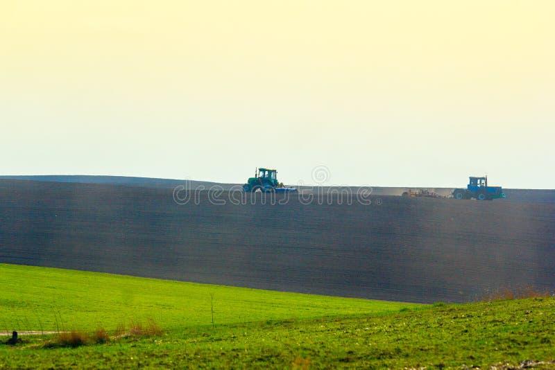 Tracteur cultivant le champ au ressort photos libres de droits