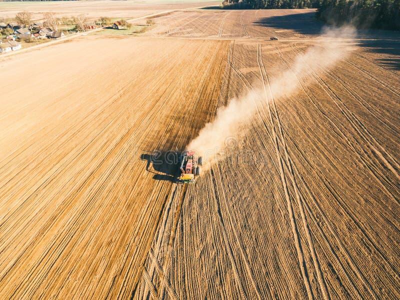Tracteur cultivant le champ au ressort photographie stock libre de droits