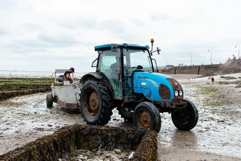 Tracteur dans la ferme d'huître à marée basse dans Cancale images stock