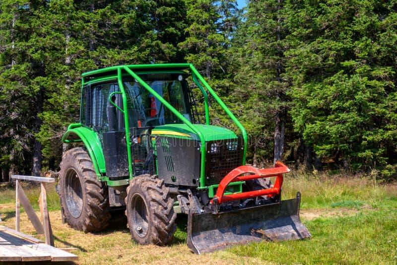 Tracteur de forestier vert avec la cage et la charrue de petit pain photos libres de droits