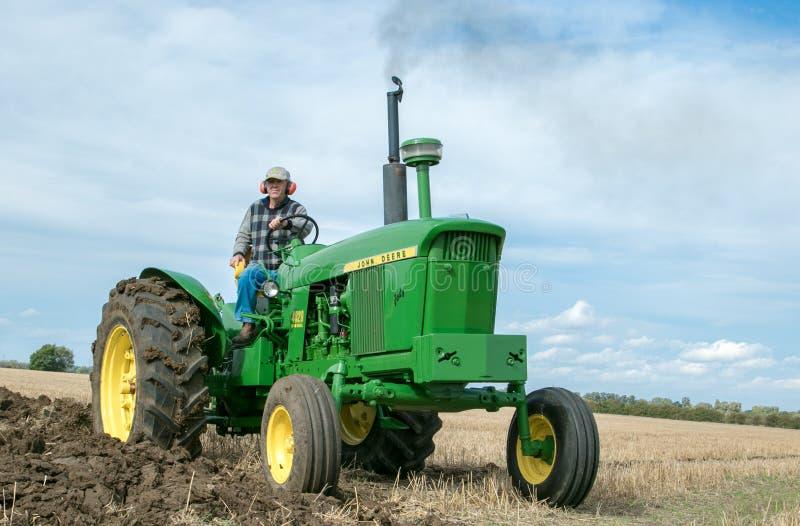 Tracteur de John Deere de vintage tirant une charrue photographie stock libre de droits