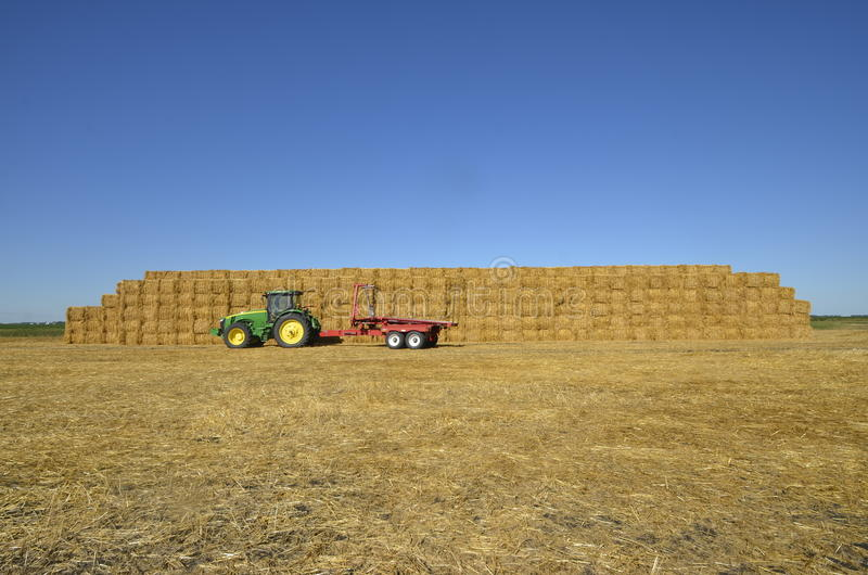 Tracteur de John Deere par la pile carrée énorme de balle photos stock