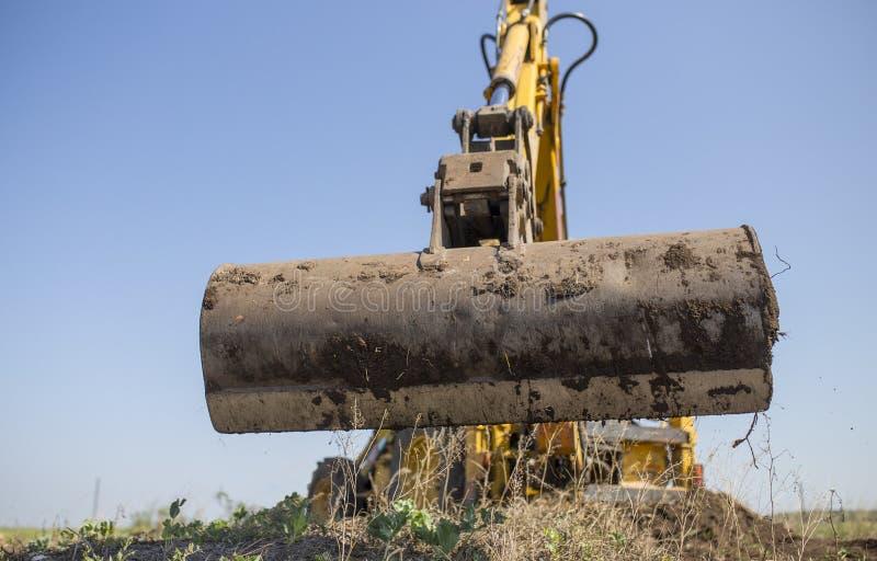 Tracteur de pelle rétro fonctionnant avec la longue pelle arrière photos stock