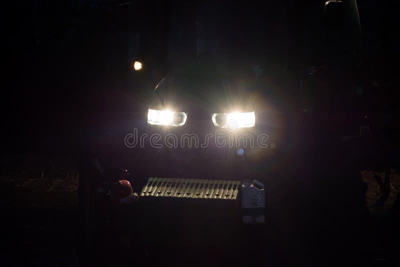 Tracteur deux labourant la terre tard la nuit avec les phares dessus image libre de droits