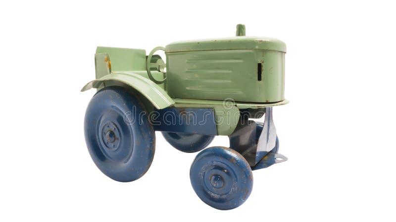 Tracteur en m?tal de vert de jouet de cru avec les roues bleues sur le fond d'isolement blanc images stock