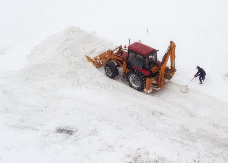 Tracteur et homme rouges avec une pelle sur le nettoyage de neige, congère photos stock