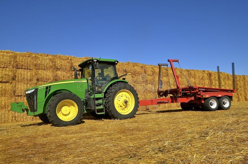 Tracteur et remorque de John Deere par la pile de balle images libres de droits