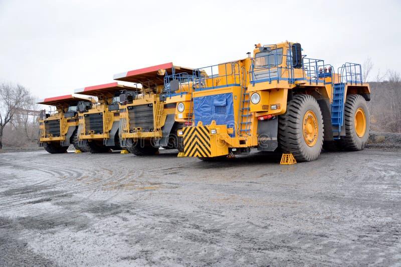 Tracteur et trois camions à benne basculante de carrière image libre de droits