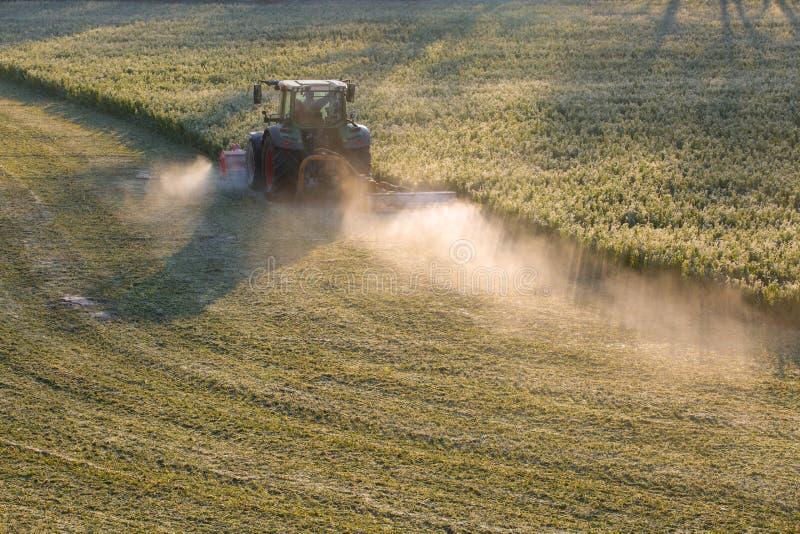 Tracteur fauchant l'herbe sur la pelouse en hiver image stock