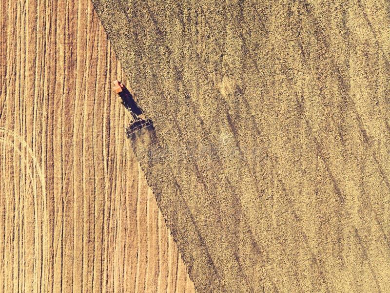 Tracteur fonctionnant dans les domaines, vue aérienne, foin sur le champ La vue à partir du dessus Le tracteur moissonne l'herbe  photos stock
