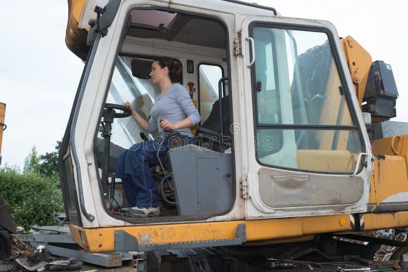 Tracteur fonctionnant de femme de brune image stock