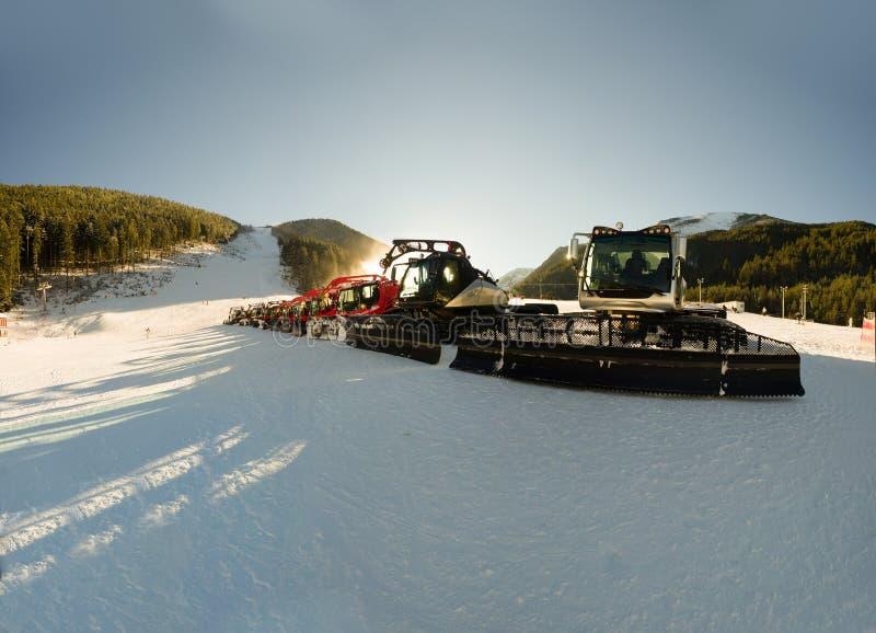 Tracteur, groupe rouge de machine de Neige-toilettage sur la colline de neige prête pour les préparations de ski de pente, Bansko photographie stock libre de droits