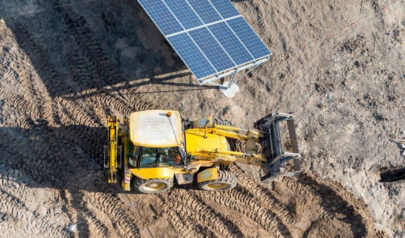 Tracteur jaune entre les rangées des panneaux solaires - une vue supérieure images stock