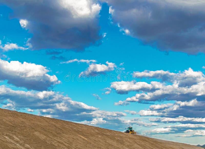 Tracteur labourant la terre contre le ciel bleu photographie stock