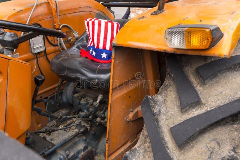 Tracteur orange de ferme avec le chapeau d'Oncle Sam image libre de droits