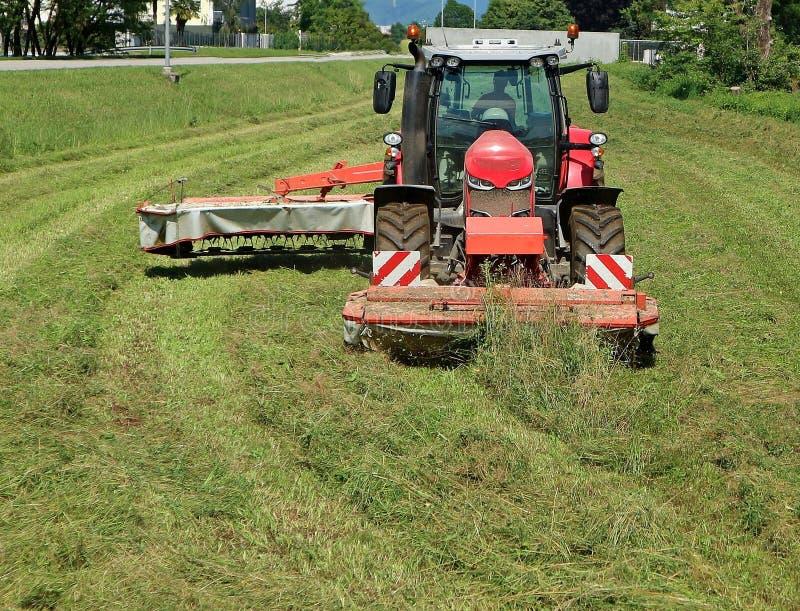 Tracteur rouge avec une faucheuse rotatoire de disque coupant l'herbe d'un champ affriché photos stock