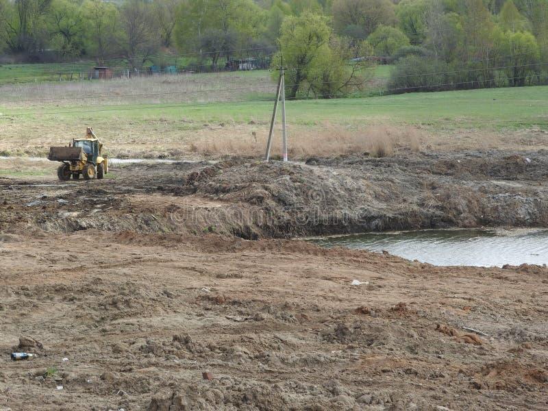 Tracteur sur le chantier de construction contre la rivi?re, les arbres et le ciel image stock