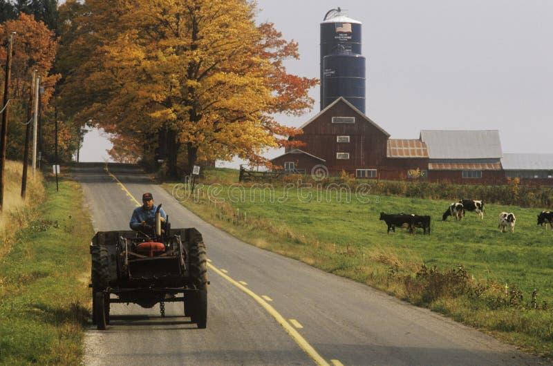 Tracteur sur le chemin d'exploitation avec la grange et le silo à l'arrière-plan en automne, VT photos libres de droits