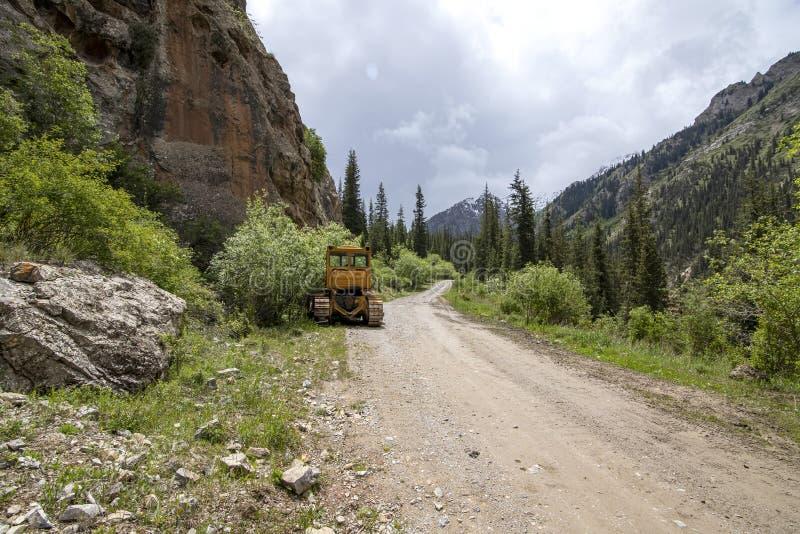 Tracteur sur une route de montagne parmi les montagnes et les forêts coniféres kyrgyzstan photo stock