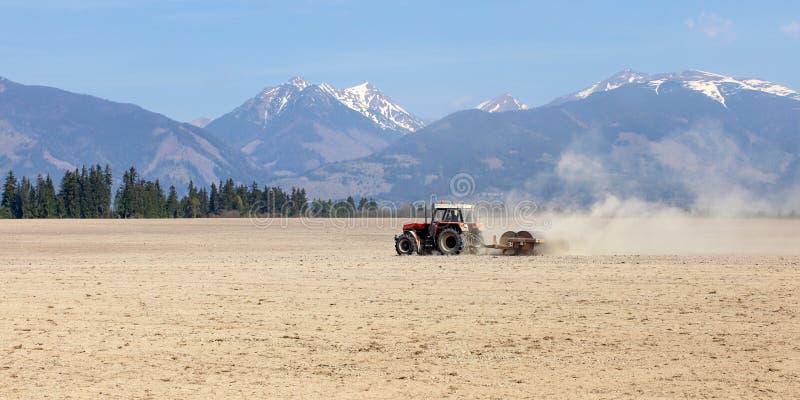 Tracteur tirant des rouleaux au-dessus des champs secs au printemps, esprit de montagnes photo stock
